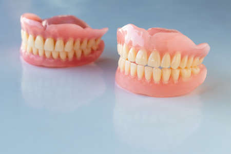 Close-up, the dentures of the two elderly were placed on a shiny table, white background to show their physical appearance.