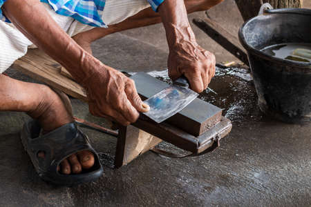 Close-up, an elderly hand sharpening knives on a whetstone, skillfully locked on a bench. 免版税图像
