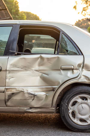 Close-up of a side door of a golden Bond car that was demolished in a collision accident with another vehicle. Foto de archivo
