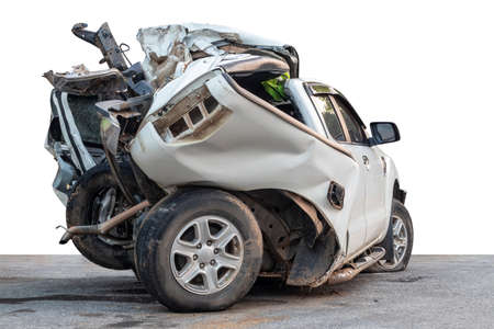 The isolate on the back of a white car was demolished in an accident and severely collided with a roadside tree as it rains, slipping wet roads, which is dangerous.