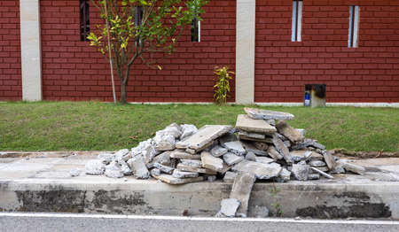 A pile of concrete rubble on the sidewalk that was demolished for repairs near the brick wall and the backyard. Stock Photo