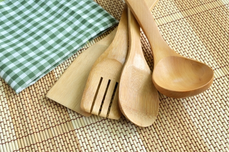 Wooden cooking utensils on wood background