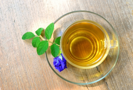 Cup of tea and purple flower on wood background
