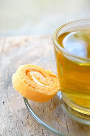 Xícara de chá com bolo de rolo no fundo de madeira Imagens