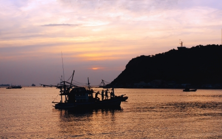 Silhouette of fisherman and boat in the bay photo