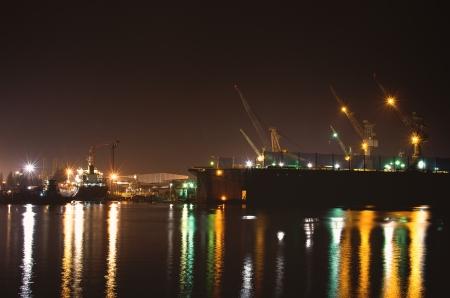 Cargo freight ship with crane bridge in repair shipyard at dusk photo