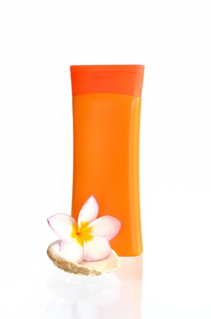 sunblock with flower and shells on white background photo