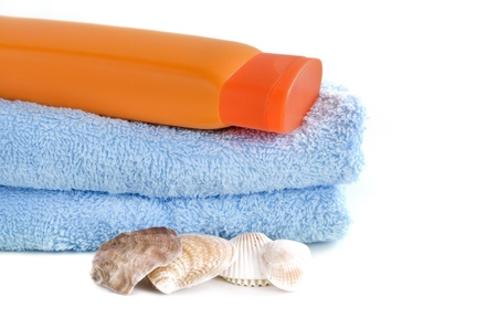 blue towel with bottle of sunblock and sea shell isolated on white Stock Photo