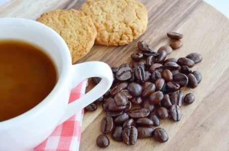 Coffee beans and cup with cookies on wooden background photo