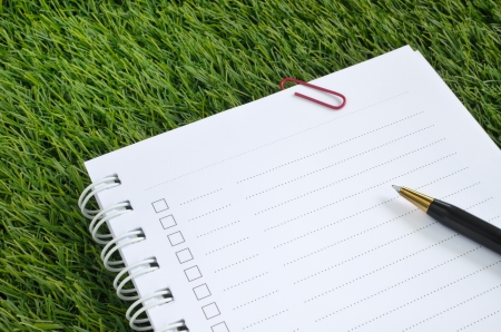 notebook and pen on the artificial grass