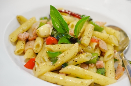 Penne pasta with ham and basil, Italian food  Stock Photo
