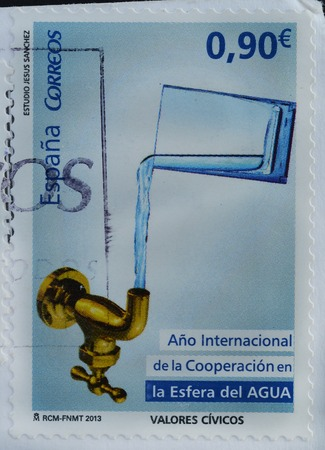 SPAIN - CIRCA 2013 : A stamp printed in Spain shows symbol the idea of a glass of water, The International Year of Water Cooperation, circa 2013 Editorial