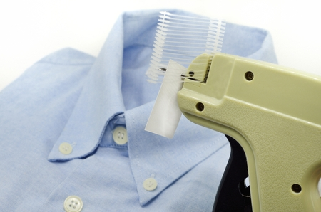 Tagging gun of cloth and blue shirt isolated on white