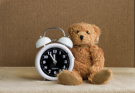 Teddy bear sitting with alarm clock on wooden and corkboard background. Stock Photo