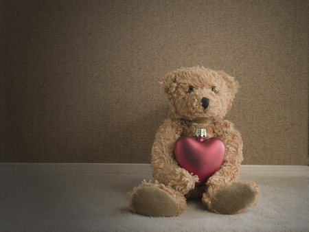Teddy bear sitting with red heart on fabric and corkboard background. vintage style Stock Photo