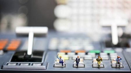 Miniature people : businessman sitting on switcher control of Television Broadcast,color buttons