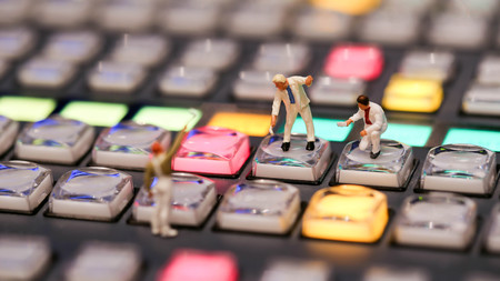 Miniature people : worker painting on switcher control of Television Broadcast,color buttons
