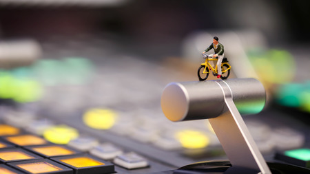 Miniature people : man riding bicycle on switcher control of Television Broadcast,color buttons. Stock Photo