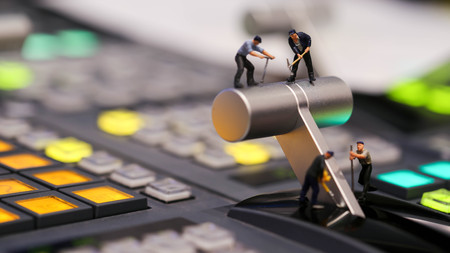 Miniature people : worker on switcher control of Television Broadcast,color buttons. Stock Photo