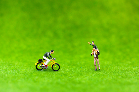 Miniature people : man ride bicycle and Son riding on fathers shoulders on green lawn background , family concept.