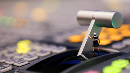 Miniature people : maid cleaning on switcher control of Television Broadcast,color buttons. Stock Photo