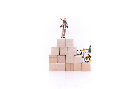 Miniature people : man ride bicycle on stack of wooden block.