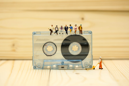 Miniature people : worker and people relax sitting with Audio cassette with magnetic tape. Imagens