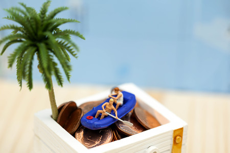 Miniature people : Travelers with paddle boat treasure coffer of gold.