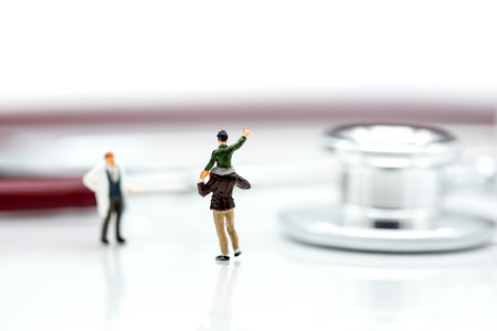 Miniature people : Doctor with father and son on stethoscope background,heathcare concept. Stock Photo