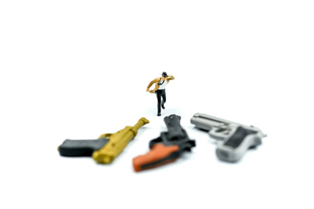 Miniature people :  businessman and Tie blowing in wind stand with gun. Stock Photo