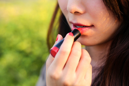 woman applying or wearing cosmetic lipstick, red ,pink ,make up and cosmetic