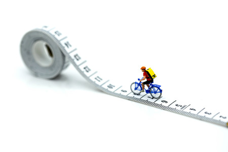 Miniature people : travelers riding bicycle with Tape Measure. Stock Photo