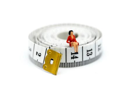 Miniature people : woman sitting on Tape Measure,Healthcare concept.