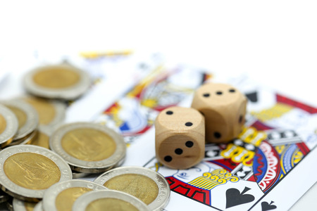 Rolls a wooden dices with coins and play card. Stock Photo