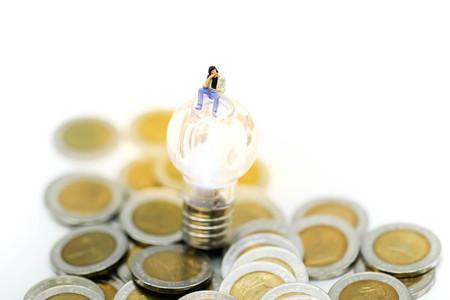 Miniature people : man sitting with coins and lamp idea,Business concept.