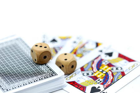 Rolls a wooden dices with coins and play card. Stockfoto