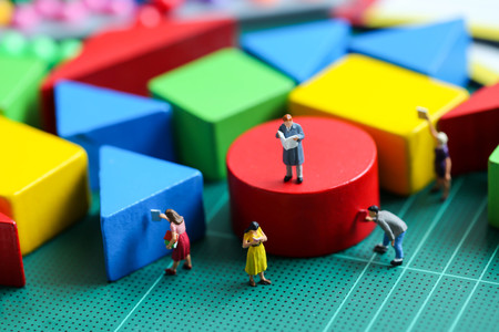 Miniature people : people reading a book  with wooden block toy, Education concept.