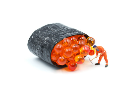Miniature people : worker with Salmon egg on sushi nigiri roll on white background. Stock Photo