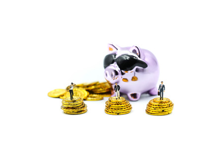 Miniature people : Businessman stand with Purple Piggy bank money  and gold coins. Stock Photo