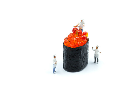 Miniature people : Chef with Salmon egg on sushi nigiri roll on white background.