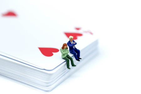 Miniature people : sitting on playing card. Stock Photo