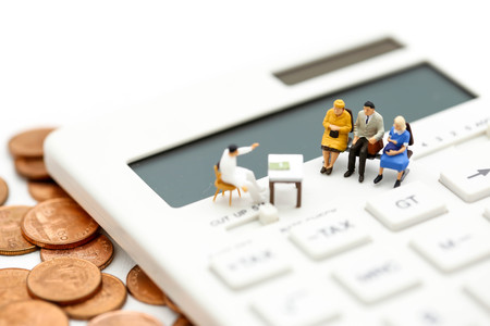 Miniature people : Couple oldman standing with Calculator,business,tax concept.