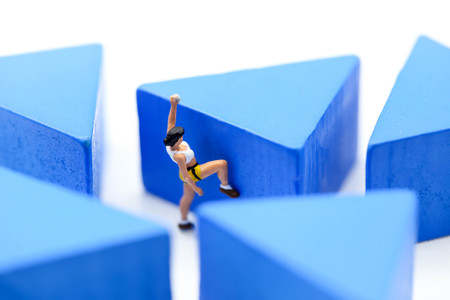 Miniature people : climbing challenging route on wooden block.