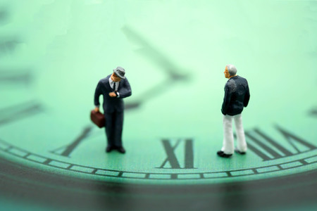 Miniature people : business man looking at watch and walk on the clock background, time business concept.