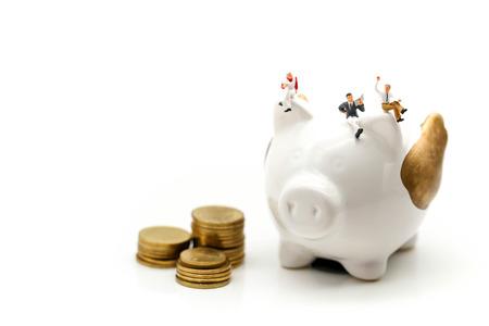 Miniature people : Businessman reading a book sitting on  Piggy bank money. Stock Photo