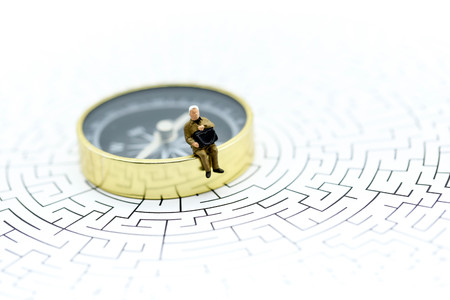 Miniature people :  businessman sitting on  compass with maze,Concepts of finding a solution, problem solving and challenge.