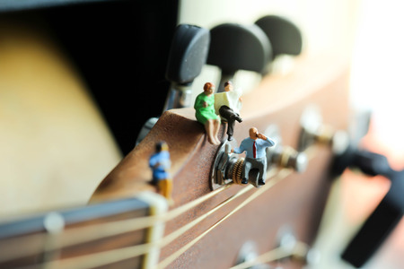 Miniature people: Businessman reading newspaper and sitting on acoustic guitar,time of relax or music relax,stationary,business concept.
