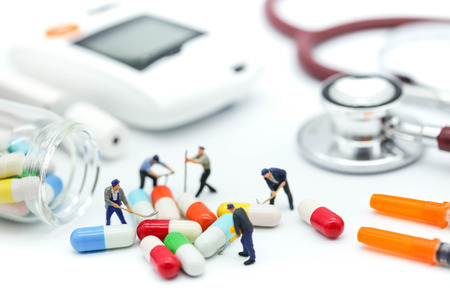 Miniature people: worker team with stethoscope and syringe and glucose meter, lancet using as background health care Medical, Check up, Medicine, diabetes, hypoglycemia concept. Stock Photo