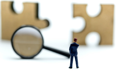 미니어처 사람들 : 사업가 직소 퍼즐 조각, 사업 비전 개념의 돋보기와 서. 스톡 콘텐츠