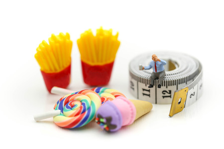 Miniature people : Fat oldman sitting on tape Measure with junkfood ,Healthcare and diet concept.